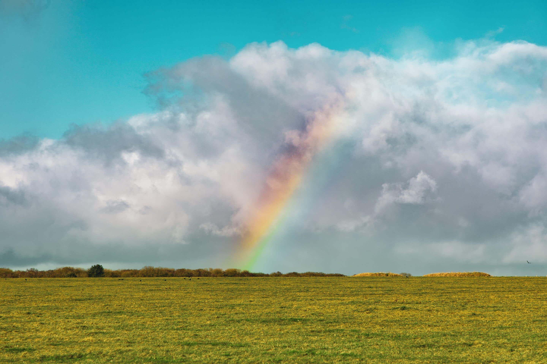 beautiful shot empty grassy field with rainbow distance blue cloudy sky
